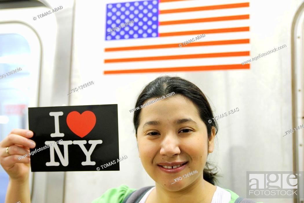 Stock Photo: Hispanic, Asian, woman holding 'I Love New York' postcard, Subway train metro station, New York City.