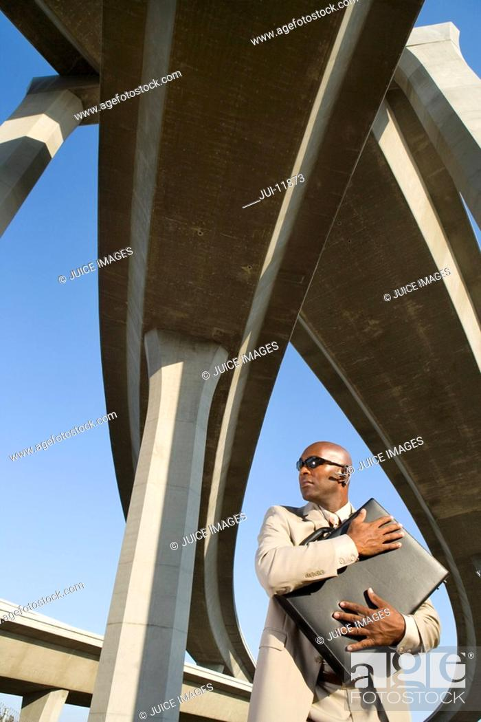 Stock Photo: Businessman embracing briefcase beneath overpasses, low angle view.