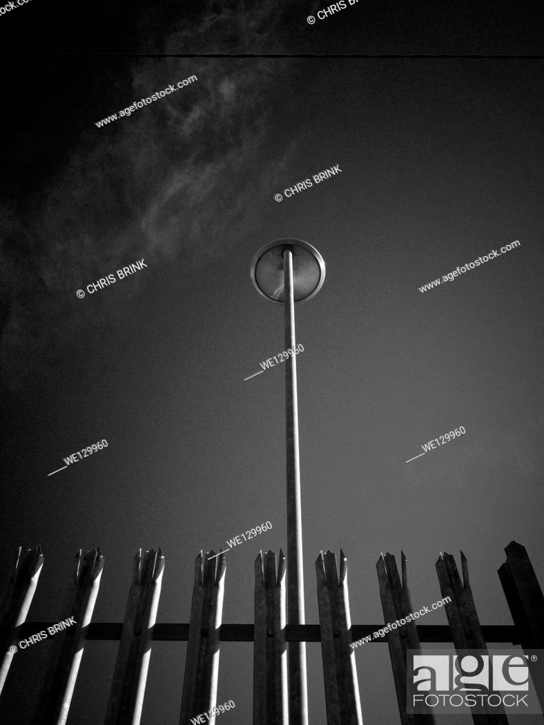 Stock Photo: Black and white image of a street light behind spikey fence in Cheshire, England, UK, Europe.