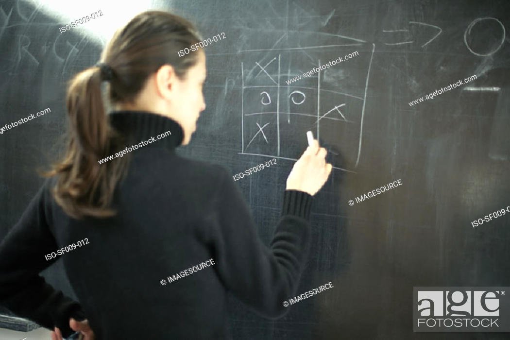 Stock Photo: Young woman drawing noughts and crosses on a blackboard.