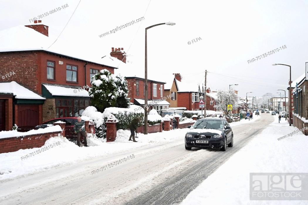 Stock Photo: City road with car in snow, Denton, Manchester, England, winter.
