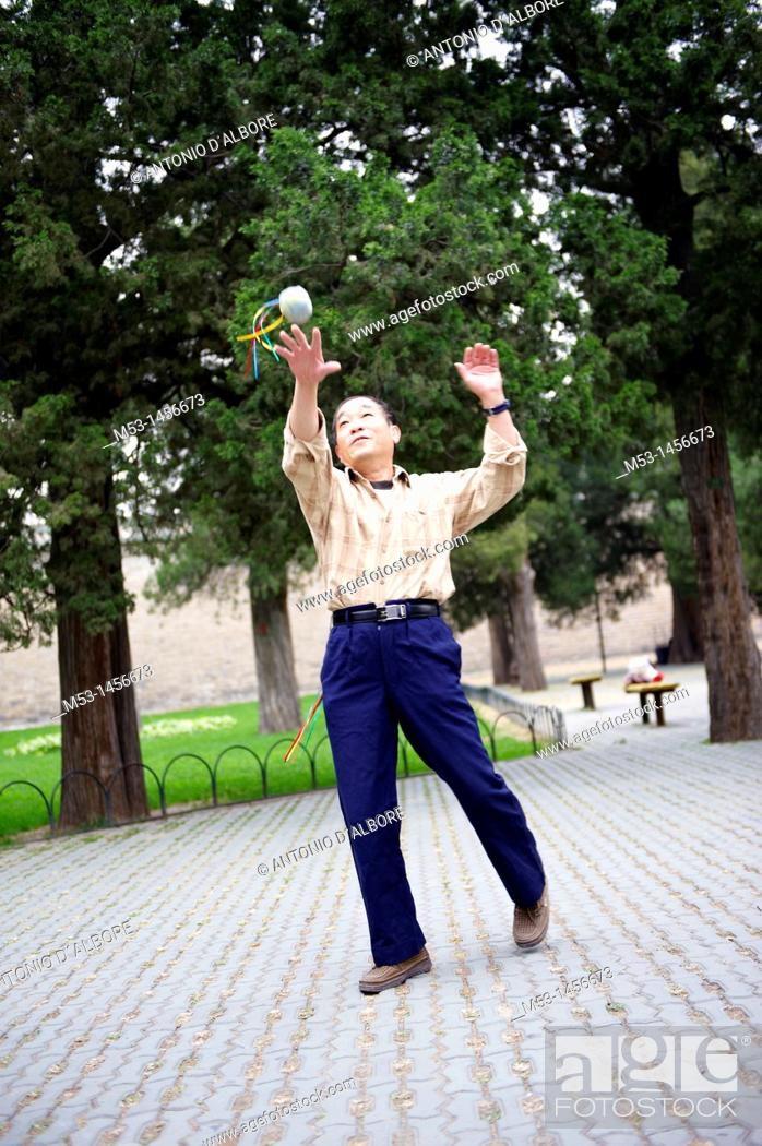 Stock Photo: A chinese man enjoy some free time juggling with a handbag in the public park of Temple of Heaven  Beijing  China.