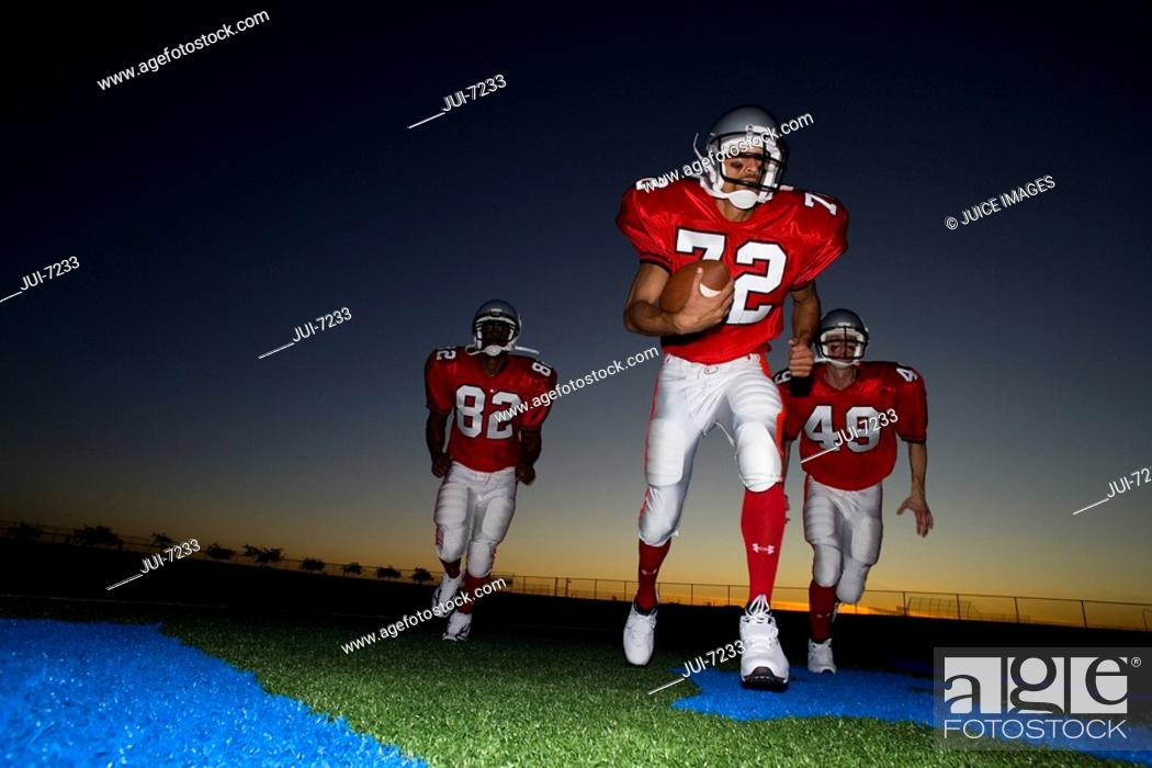 Stock Photo: Three American football players, in red strips, running on pitch with ball at sunset surface level.