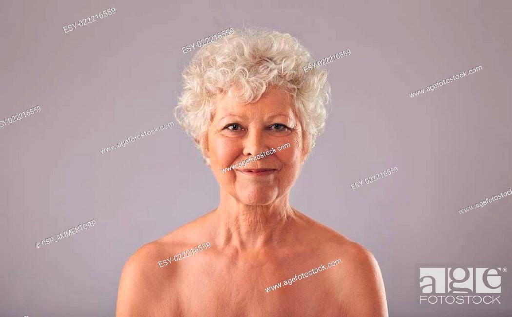 Stock Photo: Beautiful senior woman shirtless against grey background.