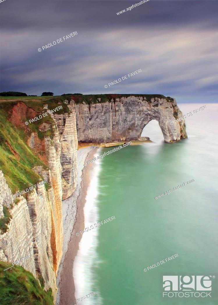Stock Photo: A moody representation, with an incoming storm in the background, of the cliff known as La Manneporte, which is part of the amazing rocky coast around Etretat.