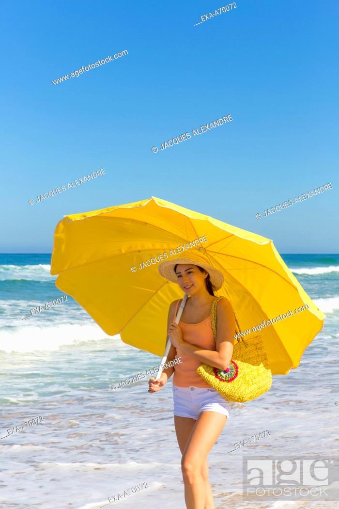 Imagen: woman walks at the beach with umbrella.