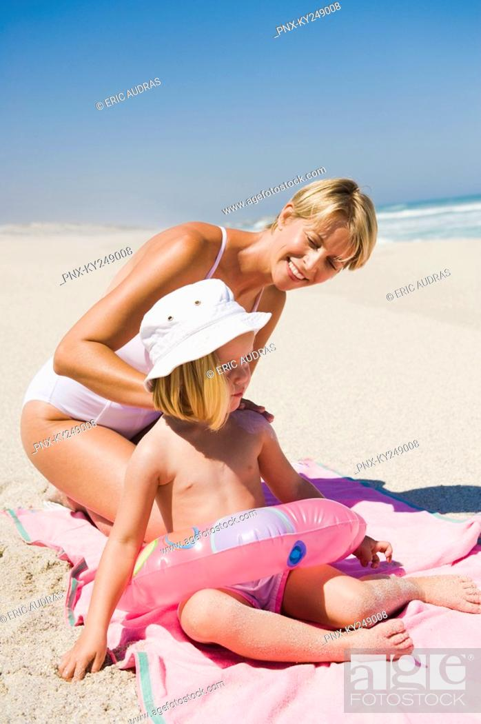 Stock Photo: Woman applying suntan lotion on her daughter on the beach.