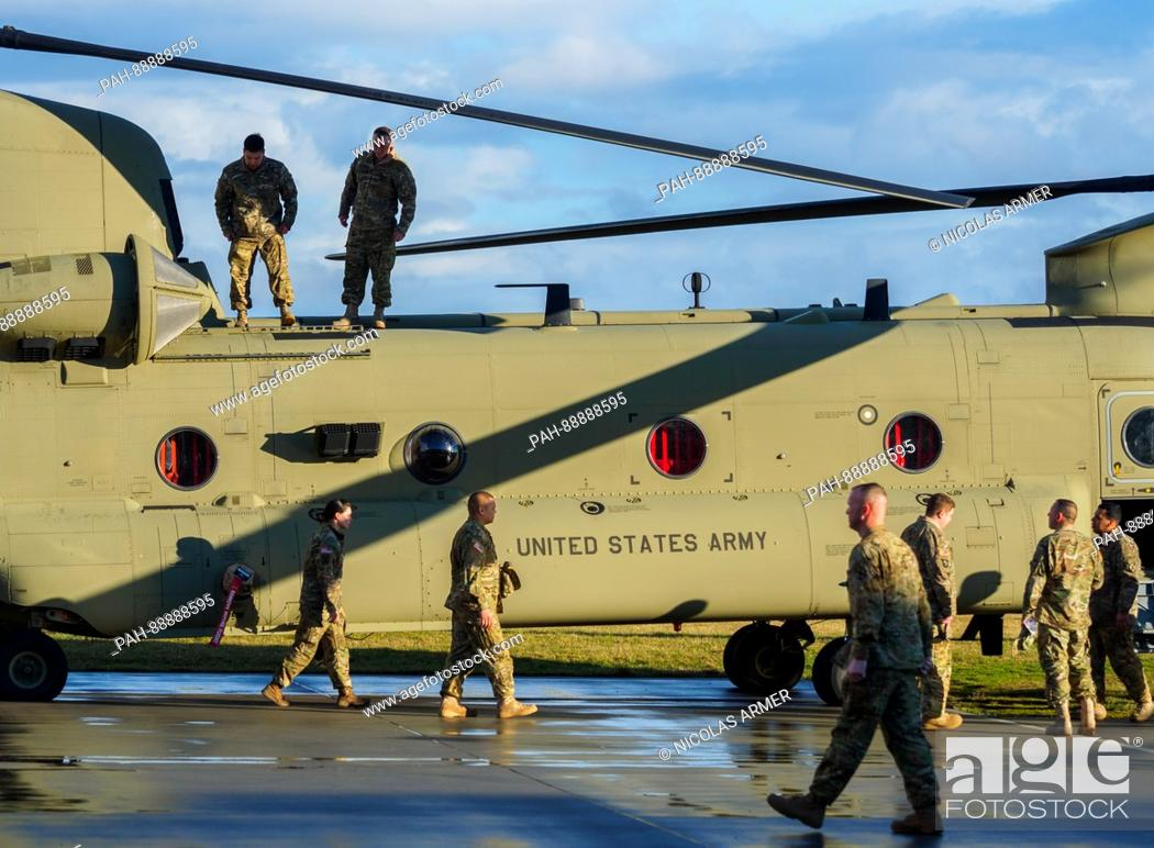 US soldiers walk past a Boeing CH-47 Chinook helicopter at
