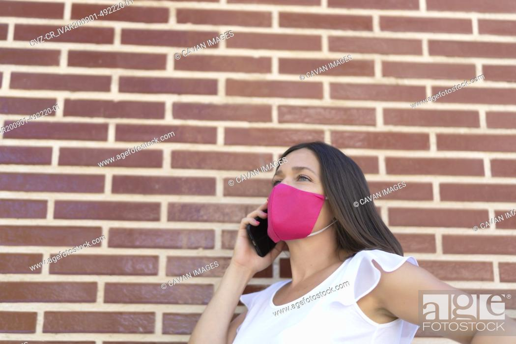 Stock Photo: beautiful woman with pink mask talking on her smartphone.