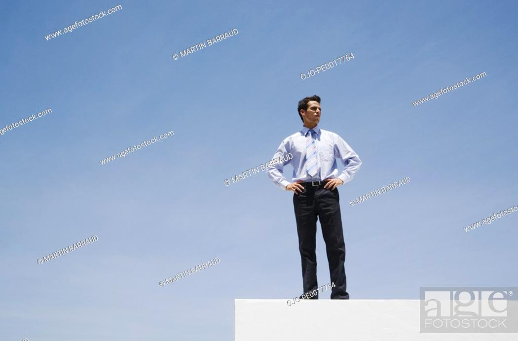 Stock Photo: Businessman standing on wall outdoors with blue sky.