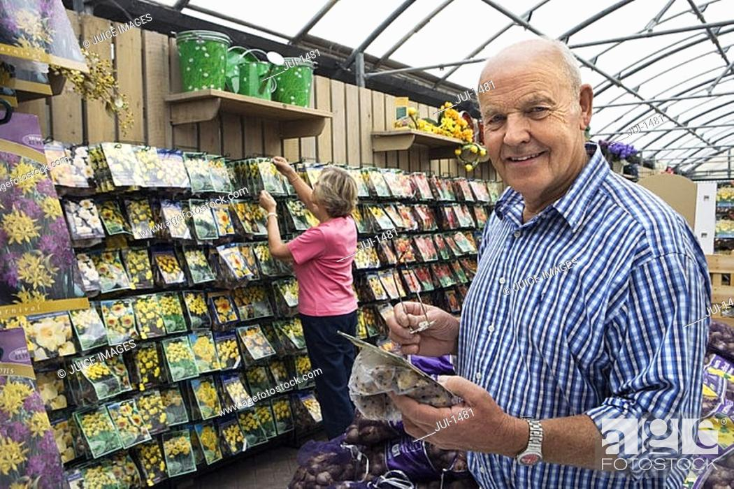 Stock Photo: Senior couple shopping in garden centre, man holding flower bulbs, smiling, side view, portrait.