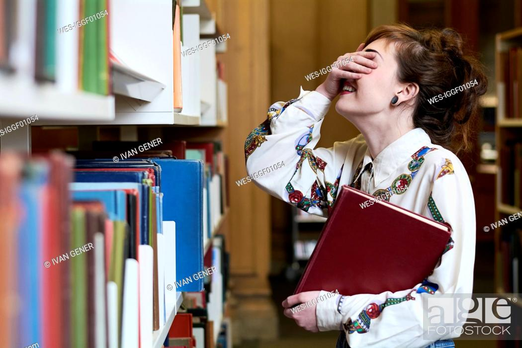 Stock Photo: Female student reading book in a public library.