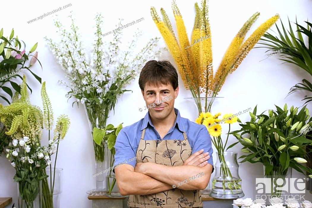 Stock Photo: Male florist in apron standing in flower shop, arms folded, smiling, front view, portrait.