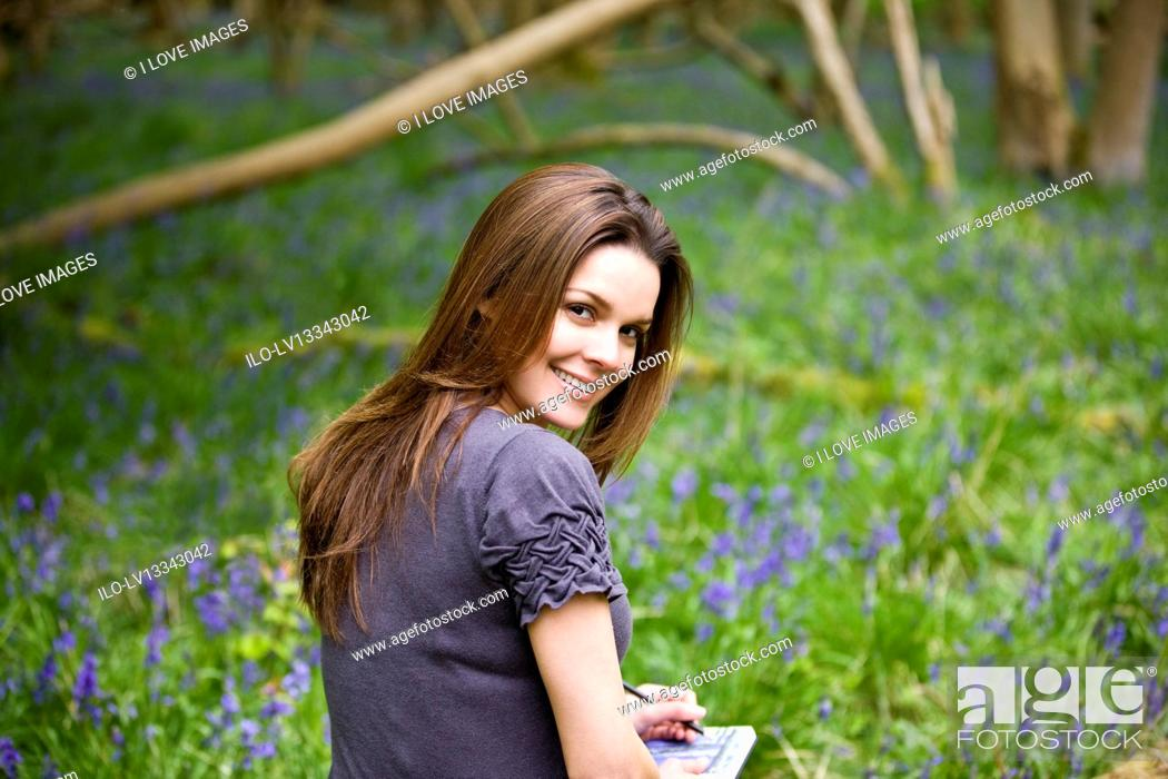 Stock Photo: A young woman drawing in a sketchbook.