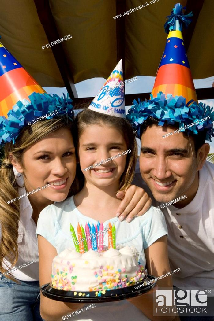 Stock Photo: Portrait of a girl with her parents holding a birthday cake and smiling.