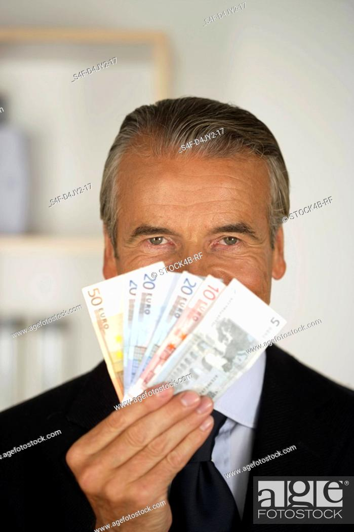 Stock Photo: Senior businessman holding banknotes.