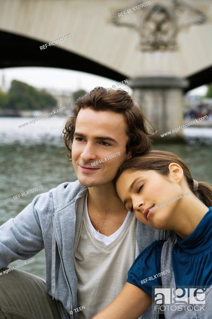 Stock Photo: Young couple sitting by river Seine, woman resting head on mans shoulder, Paris.
