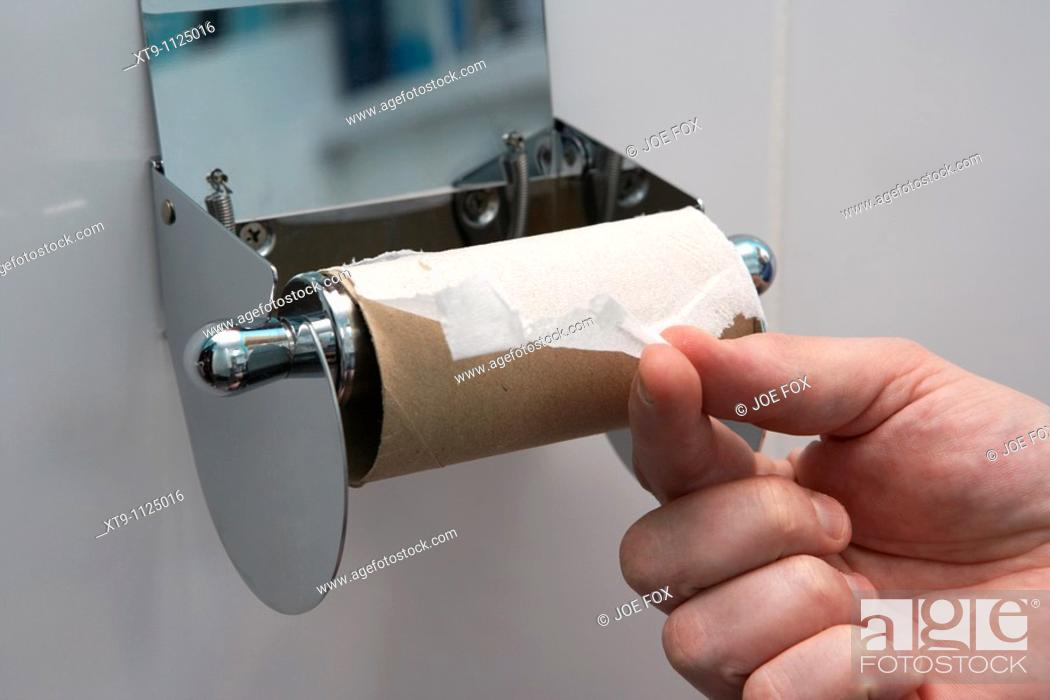 Stock Photo: mans hand pulling the last remaining sheet of toilet paper on a toilet roll holder.