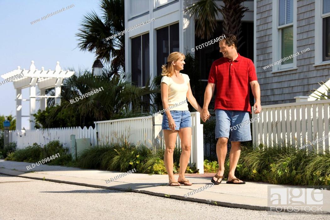 Stock Photo: Mid-adult couple walking on suburban sidewalk holding hands.