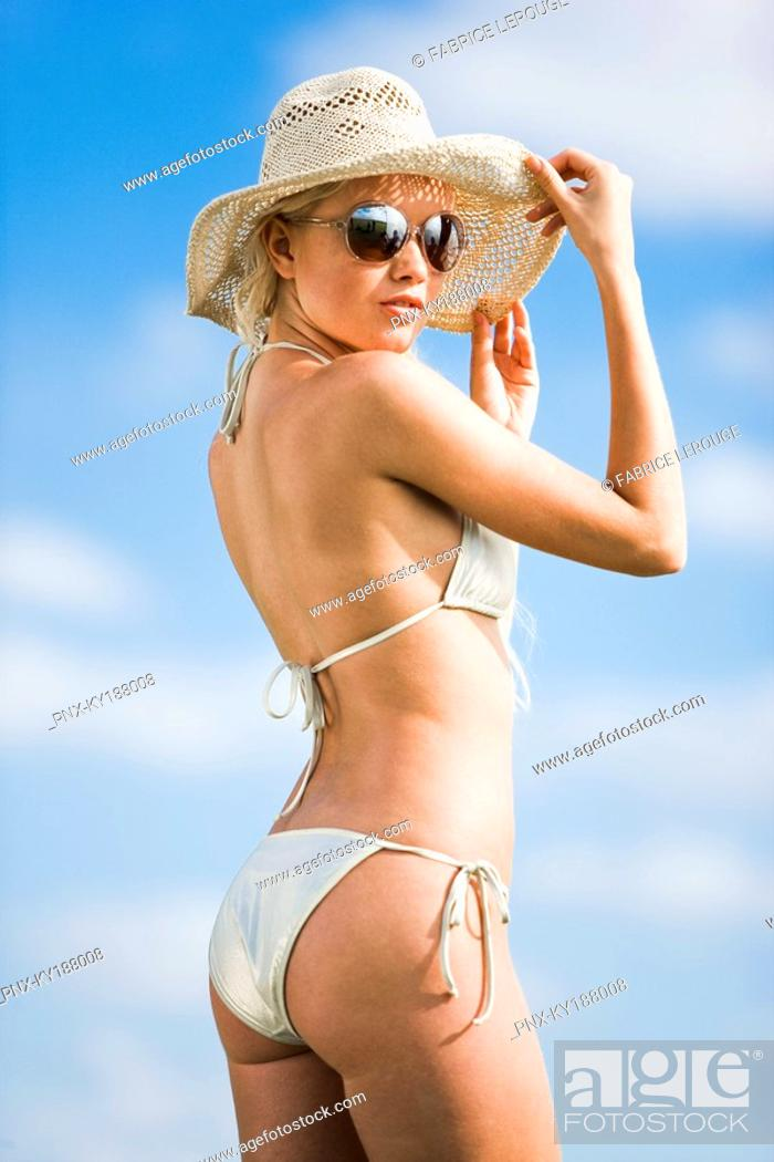 Stock Photo: Young woman wearing bathsuit, hat, sunglasses.