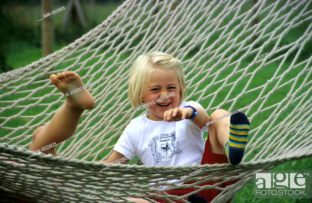 Stock Photo: A child, little girl, 5-10 years old, sitting in a hammock in the garden, laughing.