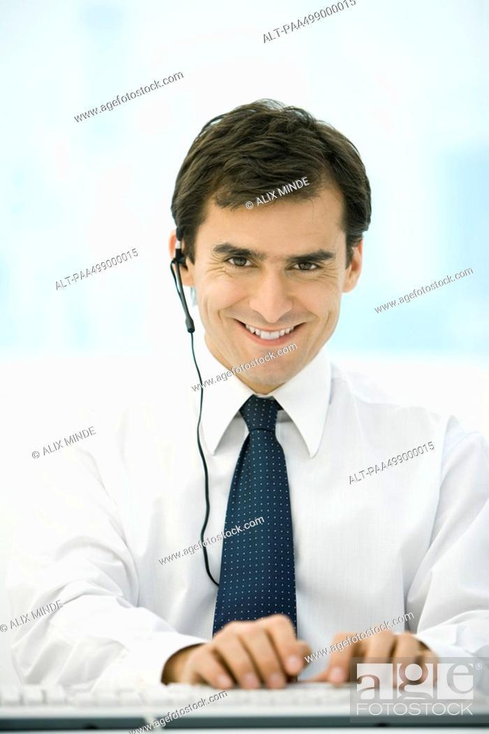Stock Photo: Man using headset and computer keyboard, smiling at camera.