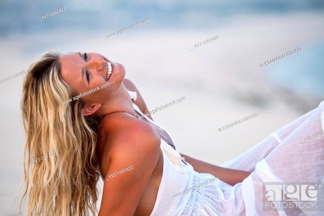 Stock Photo: Sexy blonde woman lying on the beach.