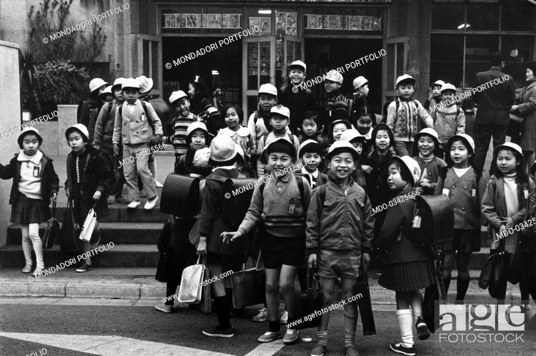 Some cheerful children leaving the school after the classes