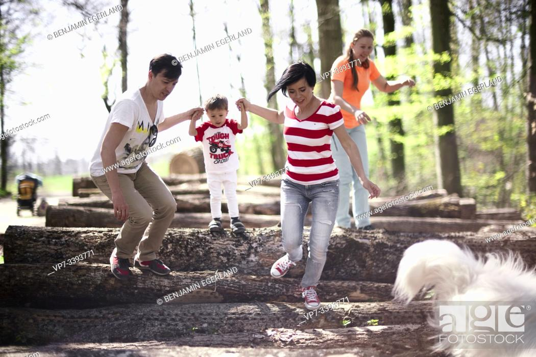 Stock Photo: parents with toddler child on hands in forest, at Herrenchiemsee, Chiemsee, Bavaria, Germany.