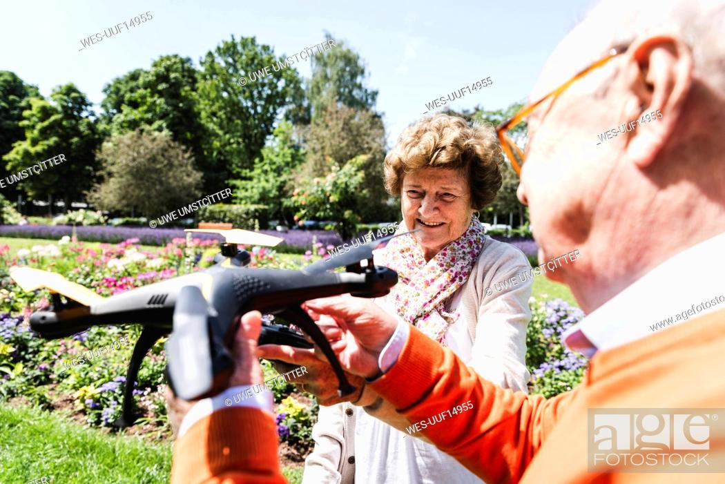 Photo de stock: Senior couple playing with a drone in park.