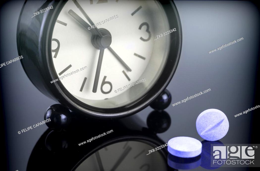 Imagen: Blue pills next to a clock, conceptual image.