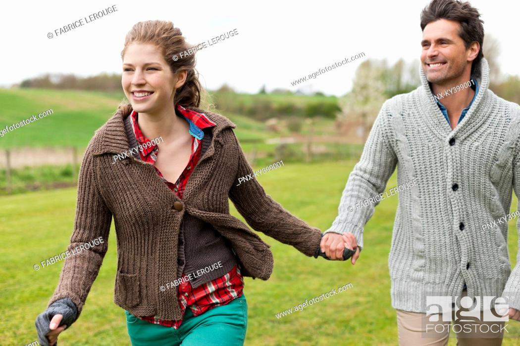 Stock Photo: Couple holding hands in a field.
