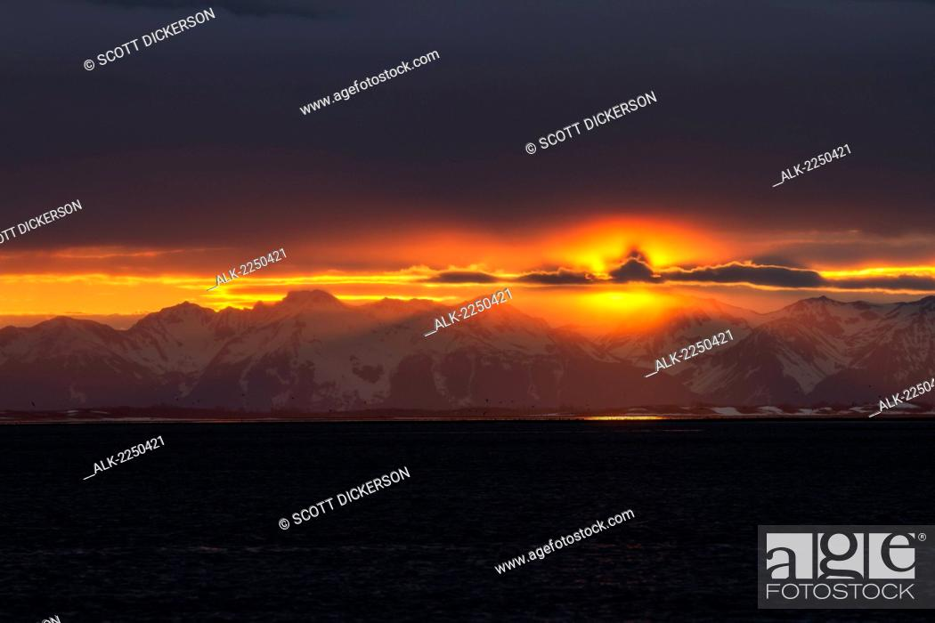 Stock Photo: A Colourful Sunset Below A Cloud Bank Over The Chugach Mountains Turns Into A Surreal Golden Glow During Low Tide On The Copper River Flats Salmon Fishing.