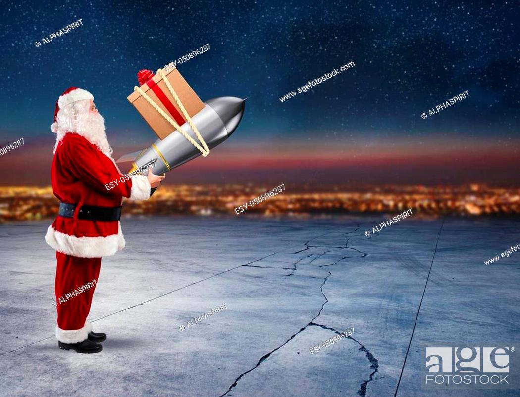 Stock Photo: Santa Claus ready to to launch a rocket with Christmas gift box in the sky.