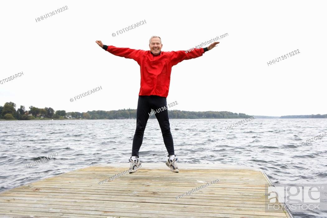 Stock Photo: Senior man jumping on jetty.