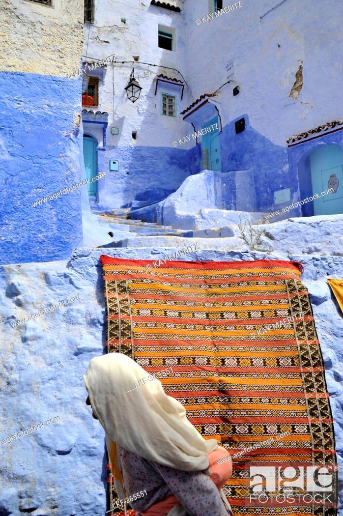 Stock Photo: Old woman in front of a carpet and blue walls in a narrow alley at Chefchaouen, Riff mountains, Morocco, Africa.