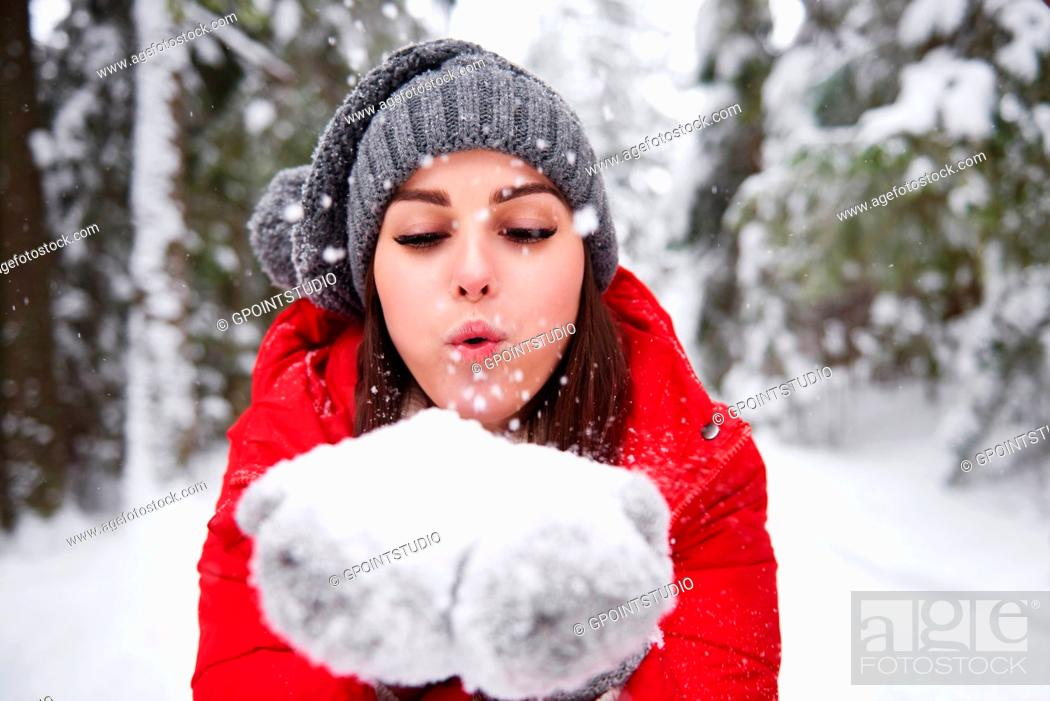 Stock Photo: Young woman blowing snowflakes off hands.