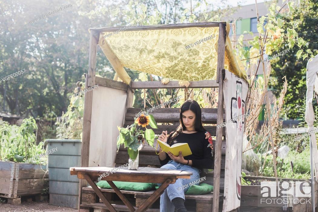 Imagen: Young woman relaxing in urban garden.