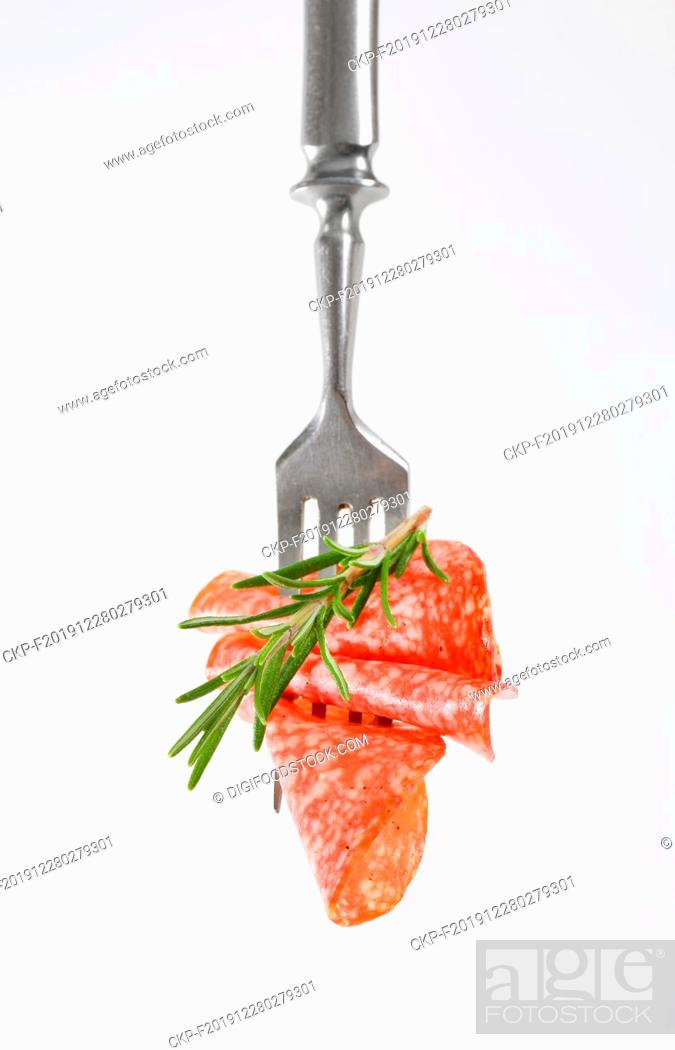 Stock Photo: Slices of Hungarian salami and fresh rosemary on fork.