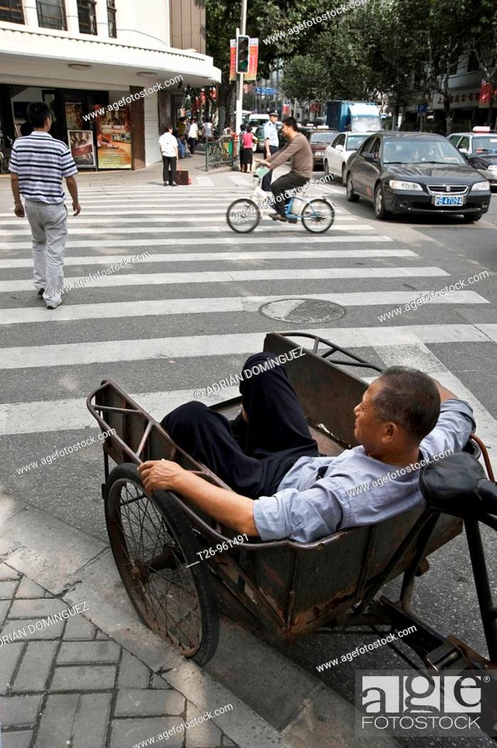 Stock Photo: a worker sits in a truck on the street. Shanghai, China.
