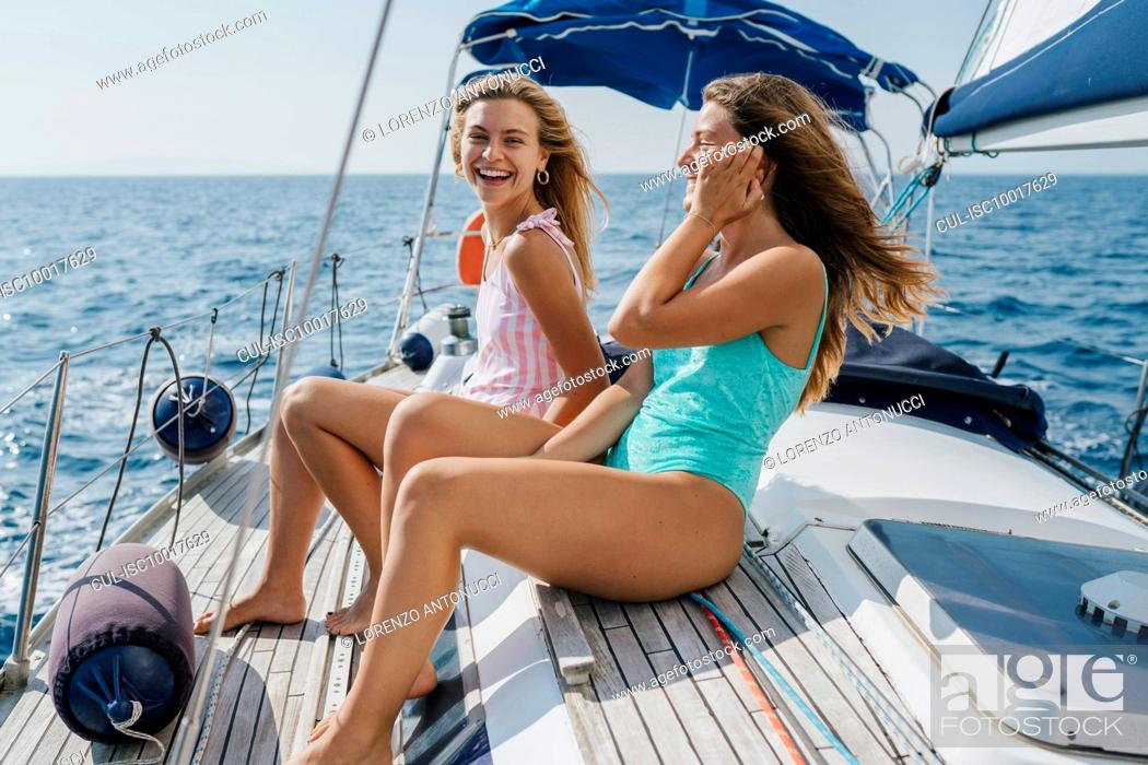 Imagen: Friends sitting on deck of sailboat enjoying sun and wind, Italy.