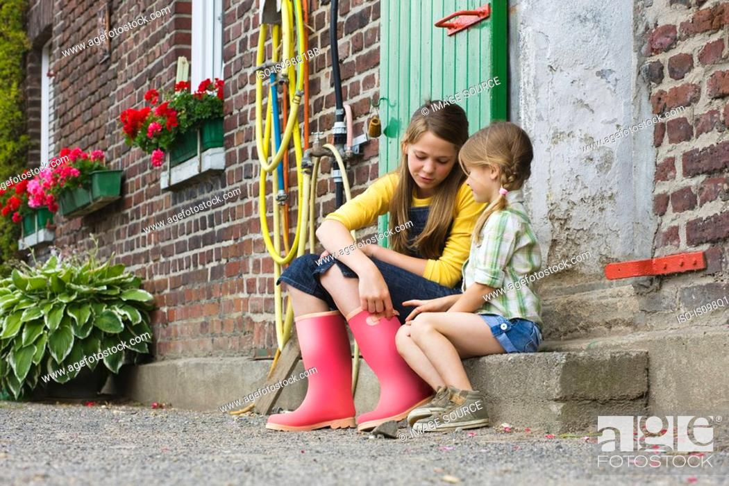 Stock Photo: Sisters sitting on a step.