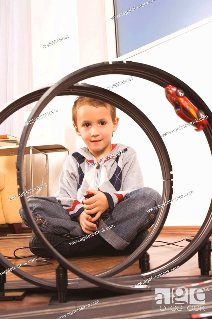 Stock Photo: Boy 4-5 playing with toy racetrack.
