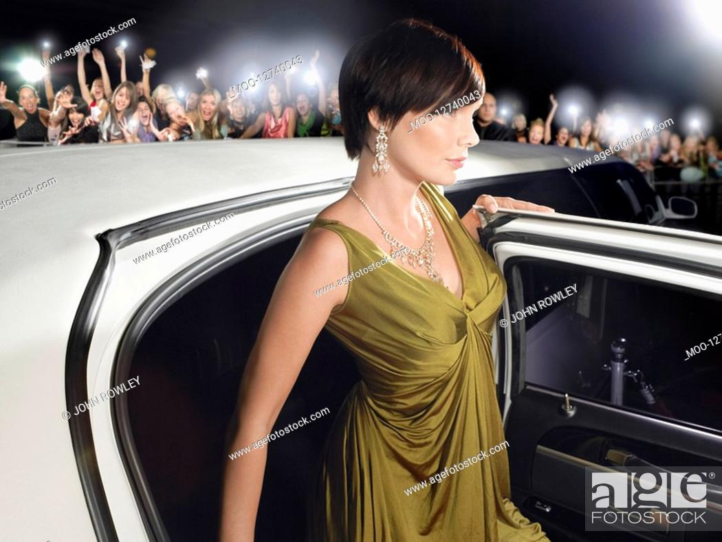 Stock Photo: Woman in evening wear getting out of limousine in front of fans and paparazzi.