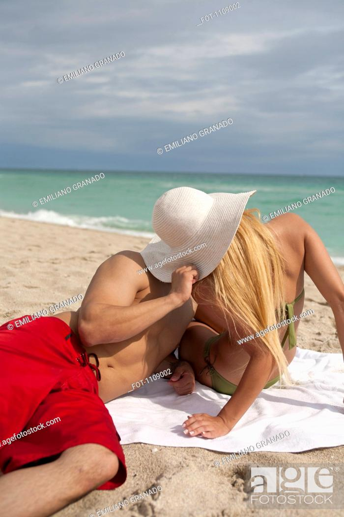 Stock Photo: A young couple kissing on the beach.