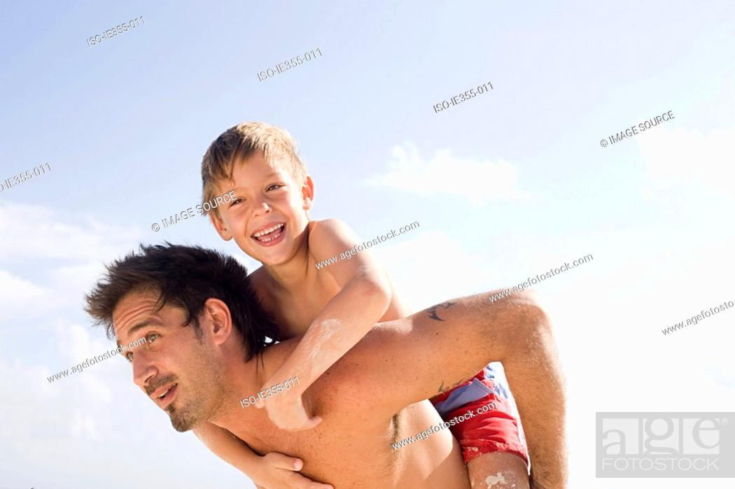 Stock Photo: A father and giving his son a piggyback.