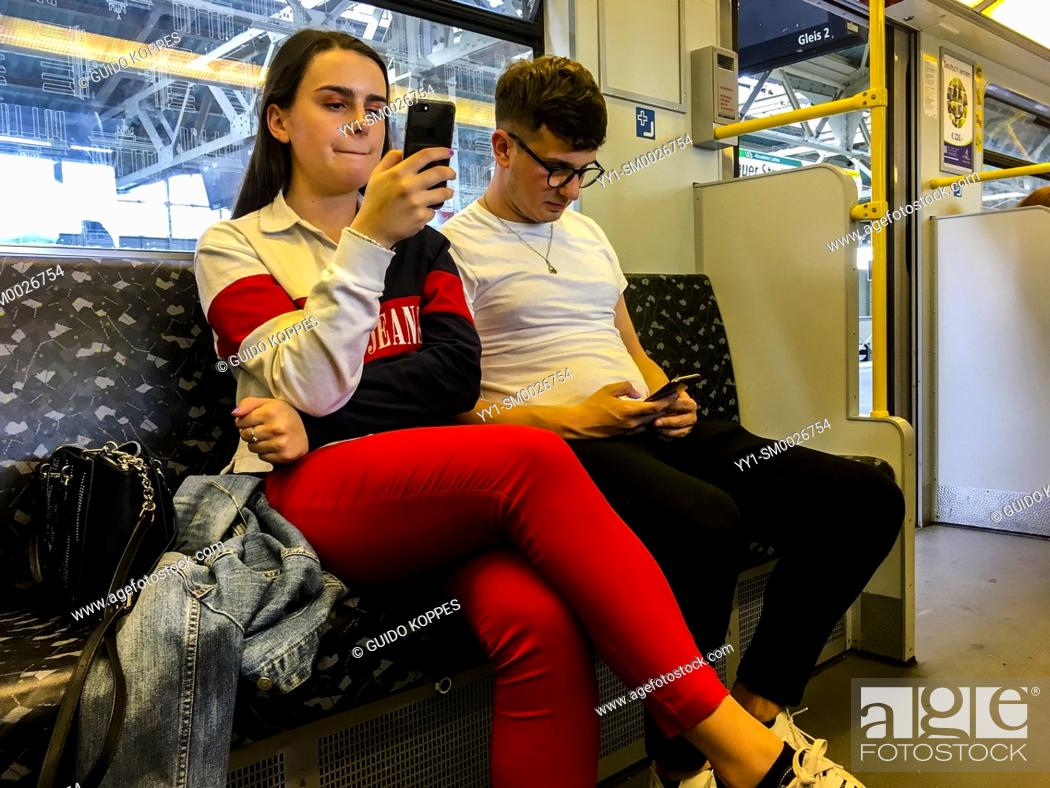 Stock Photo: Berlin, Germany. Young couple commuting by subway, having only attention for their own smartphone.