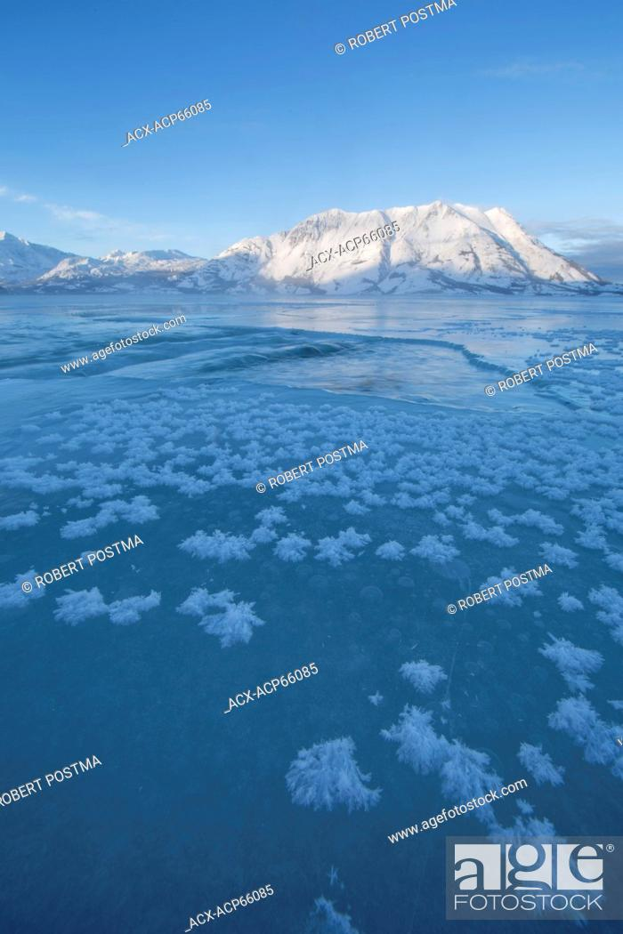 Stock Photo: Ice crystals grow on the frozen surface of Kluane Lake with Sheep Mountain lighting up in the distance. Kluane National Park, Yukon.