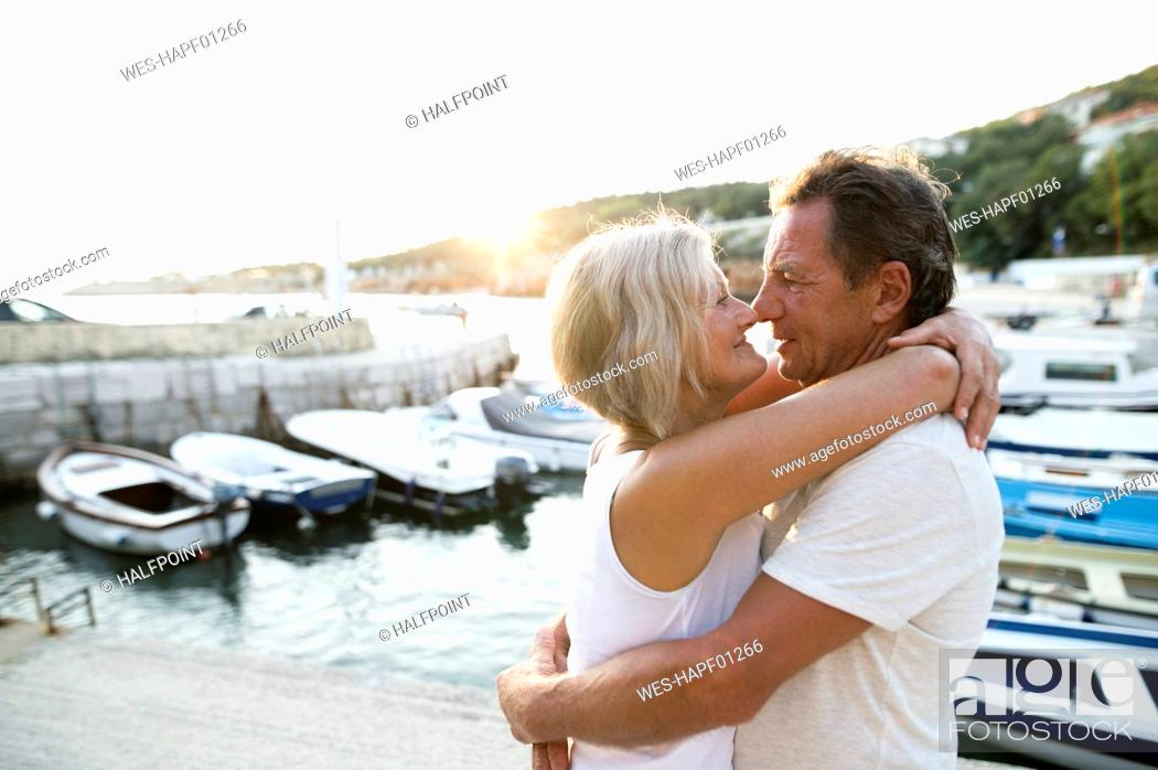 Stock Photo: Happy senior couple on quai hugging at evening twilight.