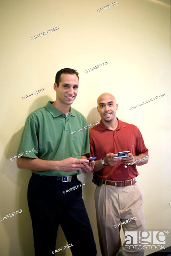 Stock Photo: Portrait of two businessmen standing in an office holding palmtops.